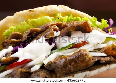 Beef Kebab in a bun with garlic sauce on woodboard - stock photo