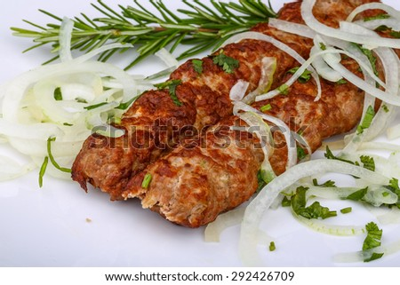 Beef Kebab with onion rings and rosemary - stock photo