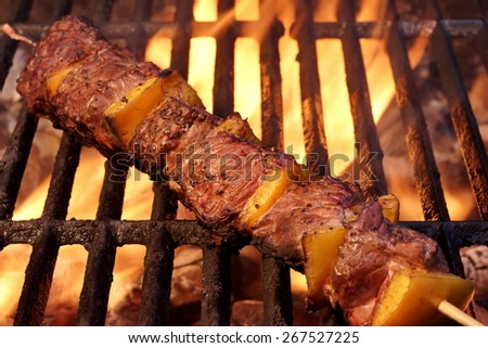 Beef Kebabs On The Hot BBQ Grill Closeup. Flaming  Charcoal Grill In The Background. Cookout Snack For Summer Spring Weekend  Barbecue or Picnic Party. - stock photo
