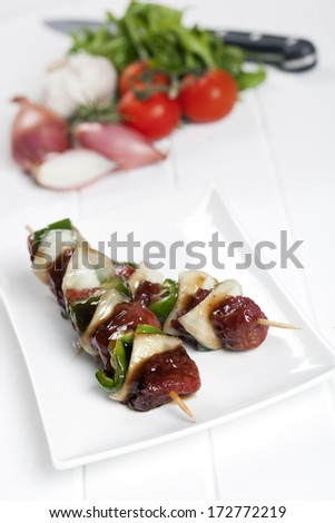 Beef kebabs, ready for cooking, with other ingredients behind. - stock photo