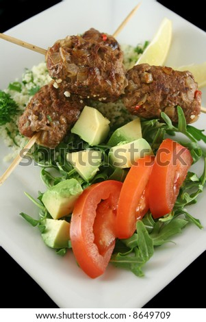 Beef koftas on parsley couscous with a garden salad. - stock photo