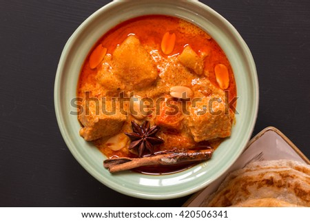 Beef massaman curry, thai cuisine eat with roti on black background, top view - stock photo