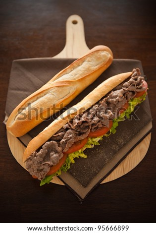 Beef meat sandwich with baguette bread on the side. Very shallow depth of field. - stock photo