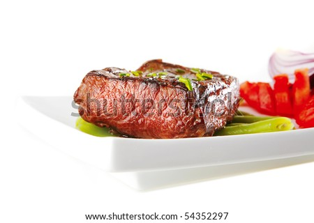 beef meat served with tomato on white porcelain - stock photo