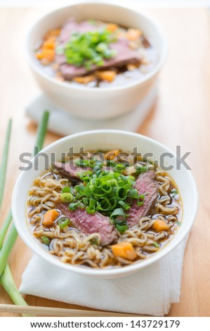 Beef noodle oriental meal in a white bowl. Very shallow depth of field. - stock photo