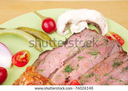 beef on plate with peppers over wooden table