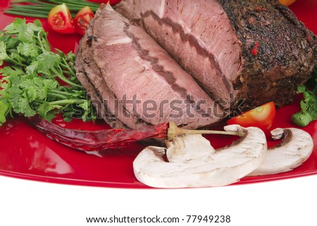 beef on red plate with vegetables over white - stock photo