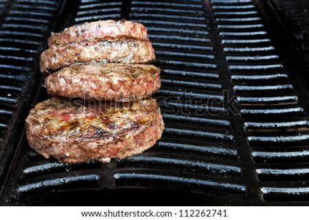 Beef quarter pounder burgers cooking on the gas barbecue - stock photo