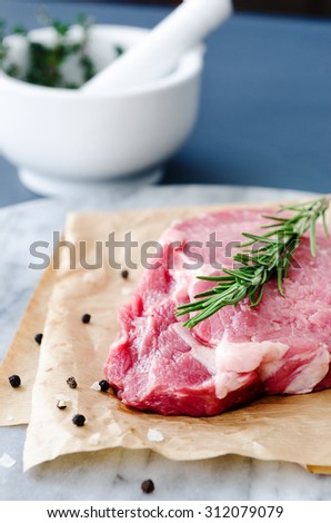 Beef rib eye steak on marble with fresh rosemary sprig - stock photo