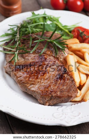 Beef rib-eye steak with french fries,rosemary and rocket salad - stock photo