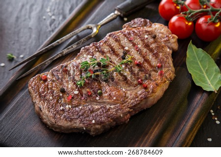 Beef rump steak on black stone table, close-up. - stock photo