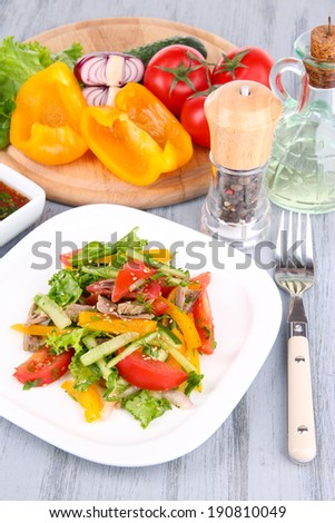 Beef salad on plate with vegetables and spices on wooden table