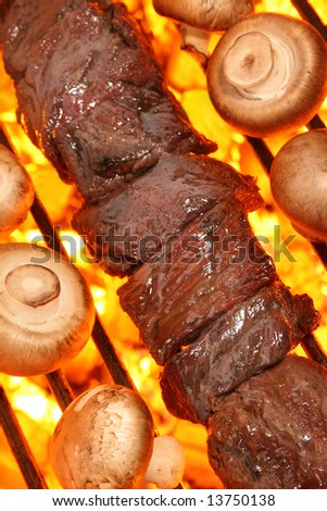 Beef shish kebab and mushrooms on a fire hot barbecue grill.