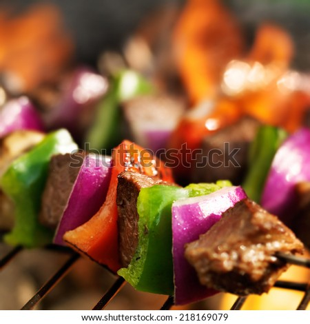 beef shish kebabs skewers cooking on grill with flames - stock photo