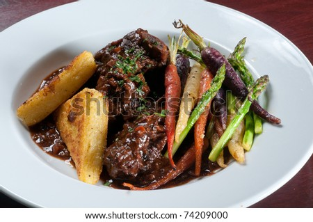 Beef short ribs with seasonal vegetables - stock photo