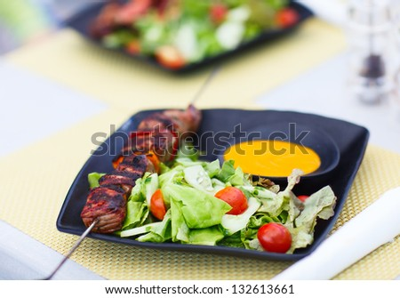 Beef skewers and fresh green salad served for lunch