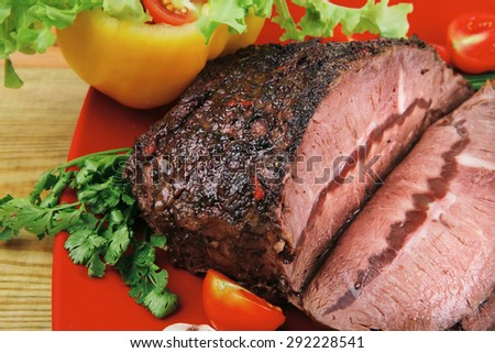 beef slice on red plate and vegetables on wood - stock photo