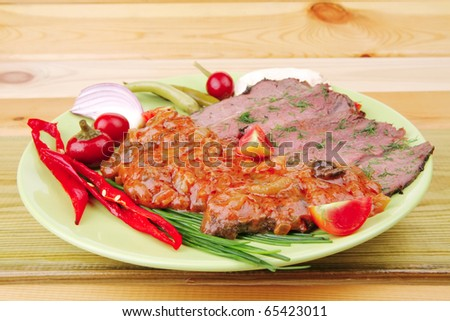 beef slices on plate over wooden table - stock photo