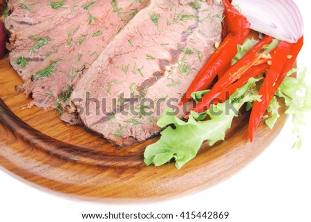 beef slices on plate with vegetables over wooden plate - stock photo
