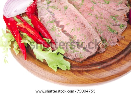 beef slices on plate with vegetables over wooden plate