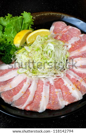Beef slices with Japanese onion, sesame, lemon and vegetable on Earthenware dish
