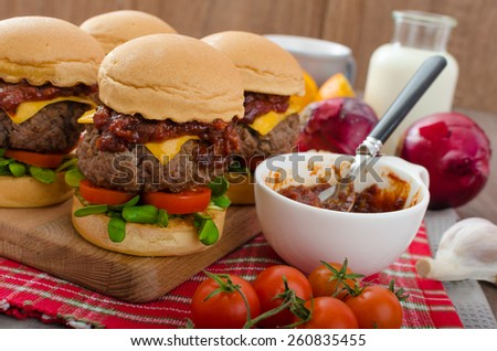 Beef Sliders with homemade barbecue sauce, cheddar, cherry tomatoes and microgreens - stock photo