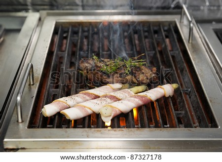 Beef steak and asparagus wrapped in bacon on coal grill