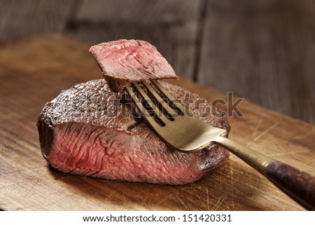 Beef steak cooked to medium rare on wooden background