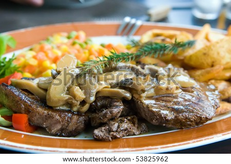 Beef steak dressed with mushroom sauce - stock photo