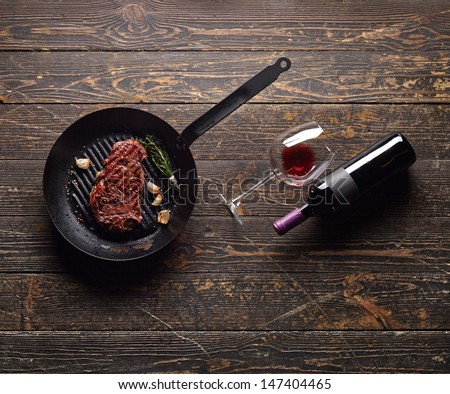 Beef steak in a grill pan with wine bottle and wine glass on old wood background. Juicy food background. - stock photo