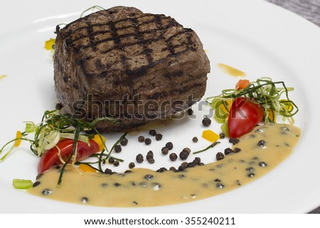 Beef steak on a plate with tomatoes - stock photo