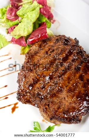 Beef steak on a white plate closeup with vegetables