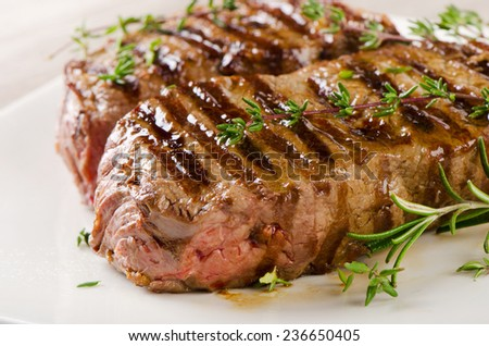 Beef steak on a  white plate . Selective focus - stock photo