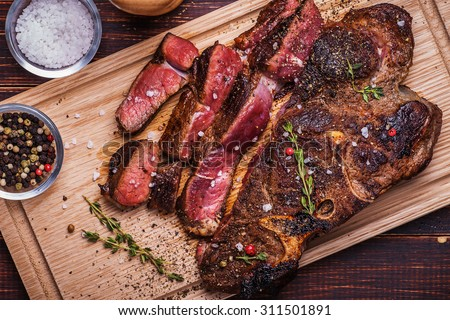 Beef steak on  a wooden background - stock photo