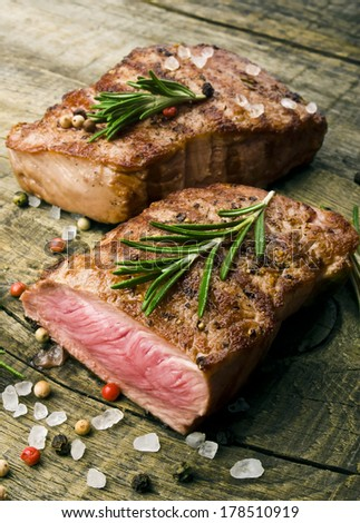 Beef steak on a wooden table. - stock photo