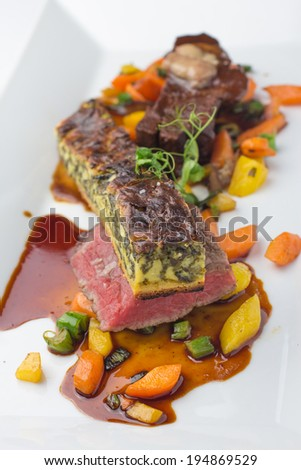 Beef steak on bed of steamed vegetables with spinach quiche