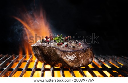 Beef steak on grill, isolated on black background - stock photo