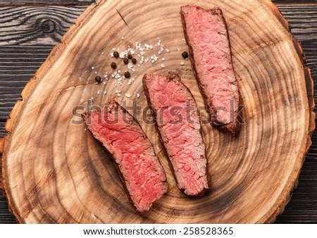 Beef steak on wooden board - stock photo