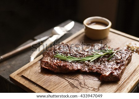 Beef steak. Piece of  Grilled BBQ beef marinated in spices and herbs on a rustic wooden board over rough wooden desk with a copy space. Top view - stock photo