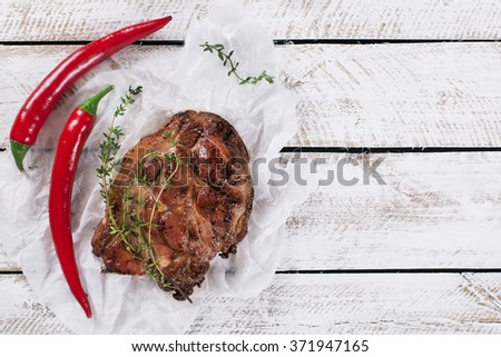 Beef steak. Piece of  Grilled BBQ beef with red chilli marinated in spices and herbs on a rustic wooden board with a copy space. Top view - stock photo