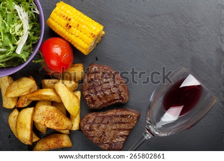 Beef steak with grilled potato, corn, salad and red wine. Top view with copy space - stock photo