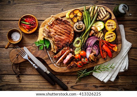 Beef steak with grilled vegetables and seasoning on serving board block - stock photo