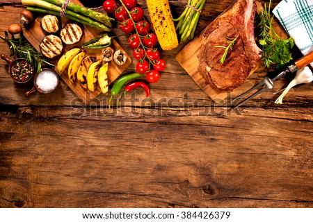 Beef steak with grilled vegetables and seasoning on wood - stock photo
