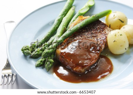 Beef steak with peppercorn sauce, baby potatoes and asparagus. - stock photo