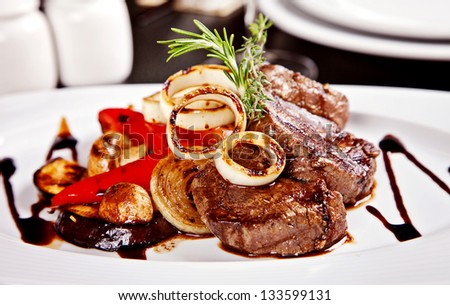 Beef steak with vegetables, rosemary and soy sause served on white plate in restaurant - stock photo