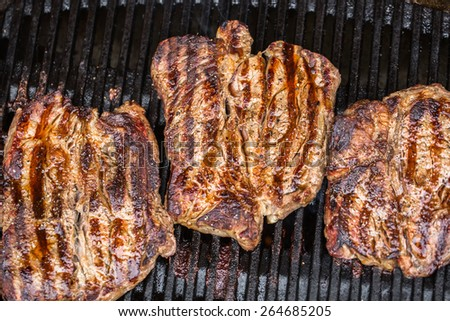 Beef steaks being prepared on grill or BBQ with pepper, spices and seasoning - stock photo