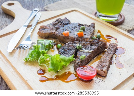 Beef steaks on wooden cutting board on wooden table. - stock photo
