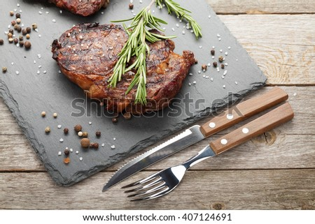 Beef steaks with rosemary and spices on wooden table - stock photo