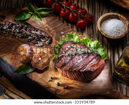 Beef steaks with spices on a wooden tray. Barbecue food. - stock photo