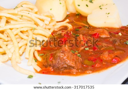 Beef stew on a plate with potatoes and pasta. Goulash is a stew which comes from Hungary. - stock photo
